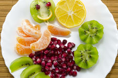 Oranges, lemons, kiwis and pomegranate on a plate. Sliced oranges, lemons, kiwis and pomegranate on a plate royalty free stock image