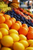 Oranges and lemons at a market stand. Oranges, lemons and other fruits at a market stand Stock Photos