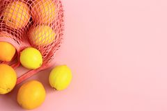 Oranges and lemons in reusable cotton net bag on pink background. Fruits in reusable cotton net bag on pastel pink background. Trendy, fashionable and stock photos