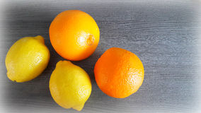 Oranges and lemons on the table. Two oranges and two lemons on the background of the gray wooden surface Royalty Free Stock Images