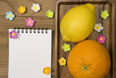 Orange and lemon. Citrus fruits. Orange and lemon. Over wood table background with opened notepad Royalty Free Stock Photo