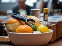 Oranges, limes, and lemons for peeling sitting in a bowl on bar to create drinks royalty free stock photography