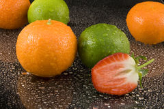 Oranges limes and strawberry. Whole oranges, limes and halved strawberry, on background of dark drops of water Royalty Free Stock Images