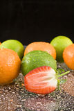 Oranges limes and strawberry. Fresh oranges and limes with halved strawberry on drops of water with black background Royalty Free Stock Photo