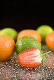 Oranges limes and strawberry. Ripe oranges, limes and halved strawberry on drops of water Stock Images