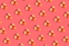 Oranges on a living coral colored background. Repeating pattern, preparation for wallpaper citrus mood. Oranges on living coral colored background. Repeating royalty free stock photography