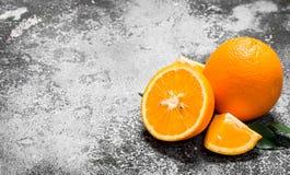 Oranges mûres avec les lames vertes Photo stock