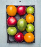 Oranges, mangoes, apples of different varieties in a wooden box wooden rustic background top view close up Royalty Free Stock Photos