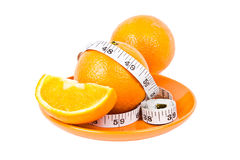 Oranges in measuring tape on plate Stock Image