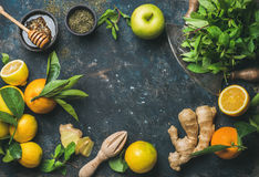 Oranges, mint, lemons, ginger, honey, apple, spices over plywood background Royalty Free Stock Photography