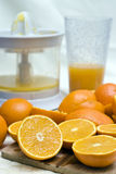 Oranges and mixer. A chopping board covered with oranges, mixer (blender) and a glass with orange juice in the background stock photos
