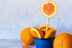 Oranges in a mug. Fresh orange slices in blue enamel mug Stock Photo