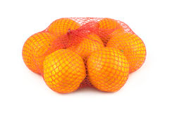 Oranges in net. Oranges in red net  on white closeup Royalty Free Stock Photography