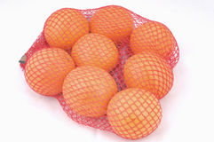 Oranges in a net. Fresh oranges in a red plastic net isolated on a white background image Stock Image
