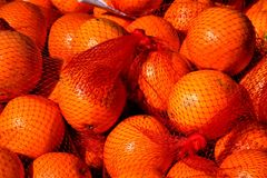 Oranges in a net bag. Background of fresh juicy oranges in a net bag on a market stall Stock Photos