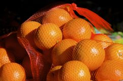 Oranges. Net bags of fresh oranges for sale in the outdoor fruit market Royalty Free Stock Photo