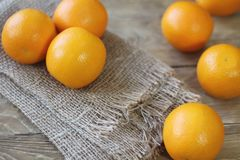 Oranges are bright orange color close-up on the right side of the frame on an old wooden background.