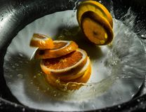 Oranges. And lemons in a bowl of water spray stock photos