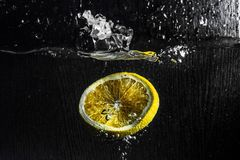 Oranges. And lemons in a bowl of water spray stock photo