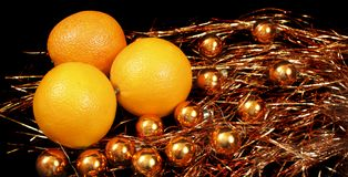 Oranges over gold Christmas balls Stock Photography