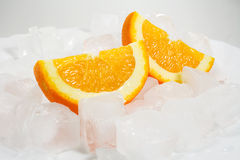 Oranges over ice. Slices of fresh oranges in between ice cubes Stock Photo