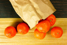 Oranges and Paper Bag. Mandarin oranges spilling out of brown paper bag onto a table covered with decorated brown striped papers Stock Photo