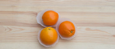 Oranges in paper small baskets on wooden texture Stock Images