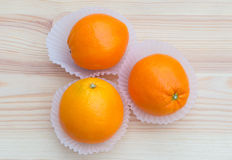 Oranges in paper small baskets on wooden texture Royalty Free Stock Photography