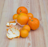Oranges in paper small baskets on wooden texture with tangerines Stock Photos