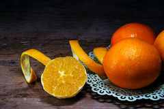 Oranges peeled and unpeeled on dark  wood Stock Image