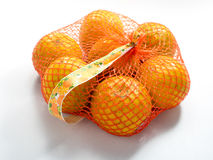Oranges in Plastic Mesh Sack on White Background.  Stock Photo