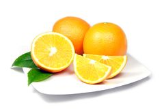 Oranges on Plate. Two Single and One Sliced Ripe Oranges on Plate Stock Photo