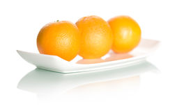 Oranges on plate  on white background. Stock Photography