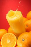 Oranges pouring Splash. On red background Stock Images