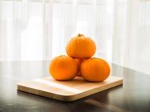 Oranges réglées sur la base en bois Photos stock