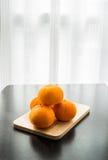 Oranges réglées sur la base en bois Images libres de droits