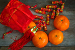 Oranges with Red Lucky Pouches and Firecracker Royalty Free Stock Photos
