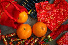 Oranges with Red Lucky Pouches and Firecracker Stock Photo