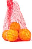 Oranges. In a red net bag on a white background Stock Photo
