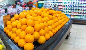 Oranges for sale in a supermarket aisle. Pile of Oranges for sale in a supermarket aisle stock image