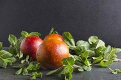 Oranges sanguines fraîches avec la menthe sur la table rustique sur le fond noir Juteux, herbes des fruits frais NAD image libre de droits