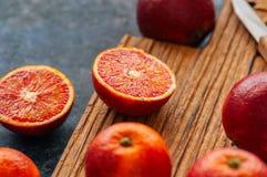 Oranges sanguines mûres fraîches entières et coupées en tranches sur un conseil en bois Cl photographie stock libre de droits