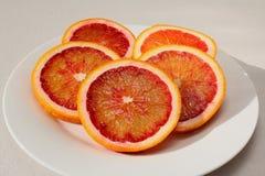 Oranges sanguines organiques coupées en tranches fraîches d'un plat Photos libres de droits