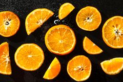Oranges, sliced on a black background royalty free stock photo