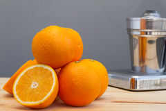 Oranges and slices with chrome citrus juicer Stock Photography
