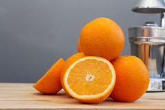 Oranges and slices with chrome citrus juicer Stock Photos