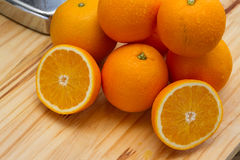 Oranges and slices with chrome citrus juicer Stock Photo
