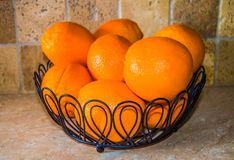Oranges stacked in a black wire bowl on kitchen counter. Oranges stacked black wire  kitchen bowl counter fruit healthy eating home options color bright kids royalty free stock photo
