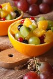 Oranges stuffed with fresh fruit salad close-up vertical Royalty Free Stock Image