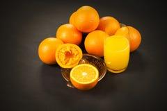 Oranges sur l'obscurité avec le presse-fruits photographie stock
